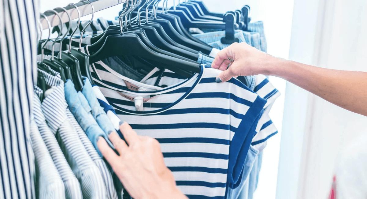 Fashion Industry Statistics - Person browsing through striped shirts