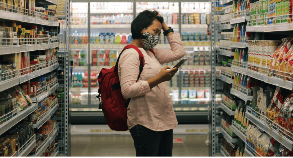 Mobile Commerce Statistics - Woman with a phone in thesupermarket
